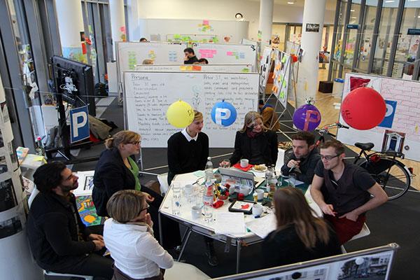 Leute am Tisch in einem Design THinking Workshop Teamspace