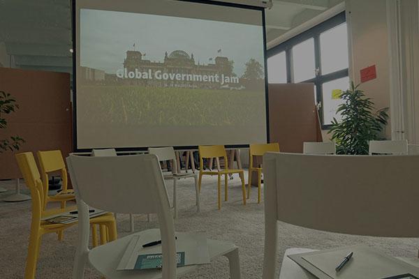 Beamer-Bild des Bundestages auf einer Leinwand mit Stühlen im Vordergrund