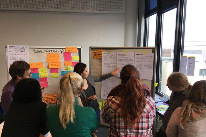 Workshopteilnehmer schauen auf ein Whiteboard während ein Coach darauf zeigt