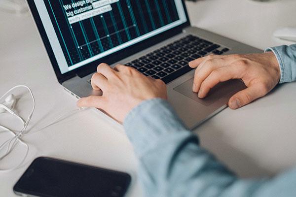 Hände arbeiten an einem Macbook
