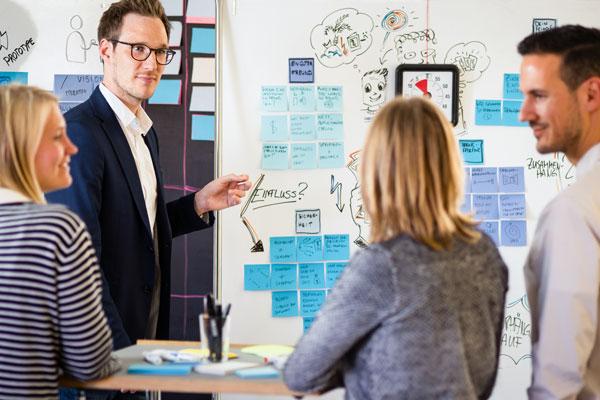 Design Thinking Coach zeigt Workshop Teilnehmern etwas auf einem Whiteboard