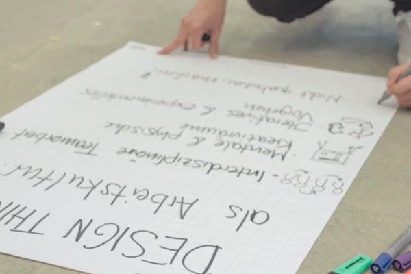 Bild eines großen Blatt Papiers, welches gerade beschreiben wird