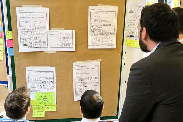 Männer schauen auf Notizen während eines Design Thinking Workshops